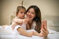 Μητέρα με την λίγο μωρό που έχει τη διασκέδαση στο κρεβάτι Χρησιμοποίηση του έξυπνου π Στοκ εικόνα με δικαίωμα ελεύθερης χρήσης