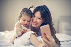 Μητέρα με την λίγο μωρό που έχει τη διασκέδαση στο κρεβάτι Χρησιμοποίηση του έξυπνου π Στοκ Φωτογραφίες