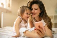 Μητέρα με την λίγο μωρό που έχει τη διασκέδαση στο κρεβάτι Χρησιμοποίηση του έξυπνου π Στοκ Εικόνα