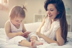 Μητέρα με την λίγο μωρό που έχει τη διασκέδαση στο κρεβάτι Χρησιμοποίηση του έξυπνου π Στοκ φωτογραφίες με δικαίωμα ελεύθερης χρήσης