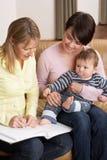 Μητέρα με την ομιλία μωρών με τον επισκέπτη υγείας σε Ho στοκ φωτογραφία με δικαίωμα ελεύθερης χρήσης