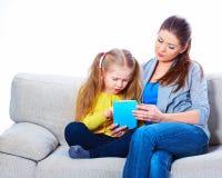 Μητέρα με τη συνεδρίαση κορών στην εκμάθηση εγχώριας εργασίας καναπέδων Στοκ Εικόνα