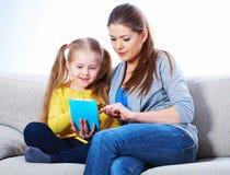 Μητέρα με τη συνεδρίαση κορών στην εκμάθηση εγχώριας εργασίας καναπέδων Στοκ Φωτογραφίες