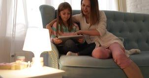 Μητέρα με τη συνεδρίαση κορών στον καναπέ που χρησιμοποιεί την ευτυχή χαμογελώντας νέα οικογένεια υπολογιστών ταμπλετών απόθεμα βίντεο