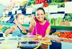 Μητέρα με τις ελιές επιλογής κοριτσιών στο κατάστημα τροφίμων Στοκ φωτογραφία με δικαίωμα ελεύθερης χρήσης