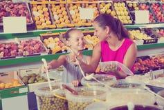 Μητέρα με τις ελιές επιλογής κοριτσιών στο κατάστημα τροφίμων Στοκ εικόνες με δικαίωμα ελεύθερης χρήσης