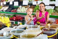 Μητέρα με τις ελιές επιλογής κοριτσιών στο κατάστημα τροφίμων Στοκ φωτογραφίες με δικαίωμα ελεύθερης χρήσης