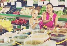 Μητέρα με τις ελιές επιλογής κοριτσιών στο κατάστημα τροφίμων Στοκ Φωτογραφίες
