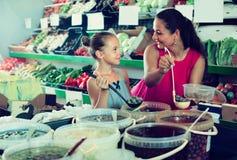 Μητέρα με τις ελιές επιλογής κοριτσιών στο κατάστημα τροφίμων Στοκ Εικόνες