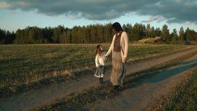 Μητέρα με τον περίπατο κορών στον αγροτικό δρόμο στο ηλιοβασίλεμα φιλμ μικρού μήκους