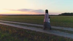 Μητέρα με τον περίπατο κορών στον αγροτικό δρόμο στο ηλιοβασίλεμα απόθεμα βίντεο