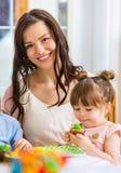 Μητέρα με το κορίτσι γενεθλίων που τρώει το κέικ Στοκ Φωτογραφίες