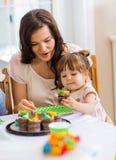 Μητέρα με το κορίτσι που τρώει Cupcake στη γιορτή γενεθλίων Στοκ εικόνα με δικαίωμα ελεύθερης χρήσης