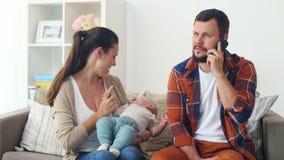 Μητέρα με το μωρό και τον πατέρα που καλούν το smartphone απόθεμα βίντεο