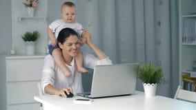 Μητέρα με το μωρό που εργάζεται στο lap-top στο σπίτι απόθεμα βίντεο