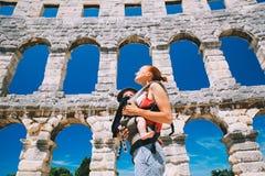 Μητέρα με το μωρό στο μεταφορέα στην παλαιά πόλη Pula, Κροατία Στοκ εικόνες με δικαίωμα ελεύθερης χρήσης