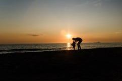 Μητέρα με το μωρό στο φως ηλιοβασιλέματος Στοκ Εικόνες