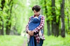 Μητέρα με το μωρό της στη σφεντόνα Στοκ Εικόνες