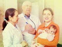 Μητέρα με τρεις μήνες μωρών και γιατροί Στοκ Εικόνες