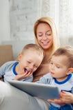 Μητέρα με δύο γιους που παίζουν με την ψηφιακή ταμπλέτα στο σπίτι Στοκ Φωτογραφία