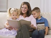 μητέρα παιδιών που διαβάζε& Στοκ Φωτογραφία