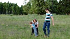 Μητέρα, πατέρας και γιος που περπατούν στο λιβάδι απόθεμα βίντεο
