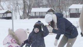 Μητέρα, πατέρας και δύο παιδιά που ρίχνουν τις χιονιές και το γέλιο απόθεμα βίντεο
