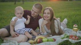 Μητέρα, πατέρας και πρώτος ελάχιστα γιος που απολαμβάνουν το πικ-νίκ τους στο πάρκο απόθεμα βίντεο