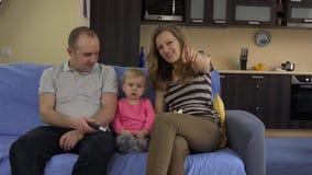 Μητέρα πατέρων και κορίτσι κορών μικρών παιδιών που εξετάζει τη συνεδρίαση TV από κοινού φιλμ μικρού μήκους