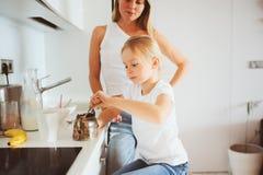 Μητέρα που έχει το πρόγευμα με την κόρη παιδιών στο σπίτι στη σύγχρονη άσπρη κουζίνα Στοκ εικόνα με δικαίωμα ελεύθερης χρήσης