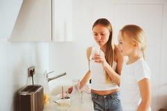 Μητέρα που έχει το πρόγευμα με την κόρη παιδιών στο σπίτι στη σύγχρονη άσπρη κουζίνα Στοκ Εικόνες