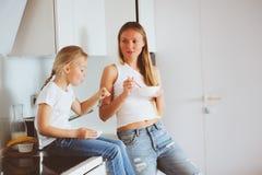 Μητέρα που έχει το πρόγευμα με την κόρη παιδιών στο σπίτι στη σύγχρονη άσπρη κουζίνα Στοκ φωτογραφία με δικαίωμα ελεύθερης χρήσης