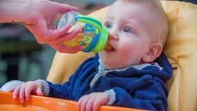 Μητέρα που δίνει ένα παιδί στο ποτό απόθεμα βίντεο