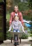 Μητέρα που δίνει το γύρο κορών Wheelbarrow στοκ εικόνα με δικαίωμα ελεύθερης χρήσης