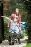 Μητέρα που δίνει το γύρο κορών Wheelbarrow στοκ φωτογραφίες