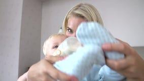 Μητέρα που δίνει το μπουκάλι γιων μωρών του γάλακτος απόθεμα βίντεο