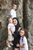Μητέρα που αγκαλιάζει τα παιδιά κοντά στο δέντρο στοκ φωτογραφίες