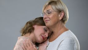 Μητέρα που αγκαλιάζει την ενήλικη κόρη που απομονώνεται στο υπόβαθρο, τη γονικές αγάπη και την υποστήριξη απόθεμα βίντεο