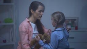 Μητέρα που αγκαλιάζει την κόρη με τη teddy αρκούδα, που πάσχει από τη φοβέρα, βροχερή ημέρα απόθεμα βίντεο