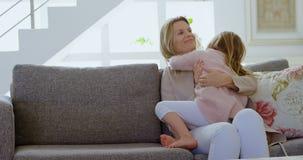 Μητέρα που αγκαλιάζει την κόρη της στο καθιστικό 4k φιλμ μικρού μήκους
