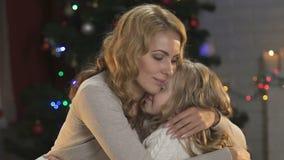 Μητέρα που αγκαλιάζει την λίγη λυπημένη κόρη που ηρεμεί, οικογενειακή προσοχή, Παραμονή Χριστουγέννων απόθεμα βίντεο