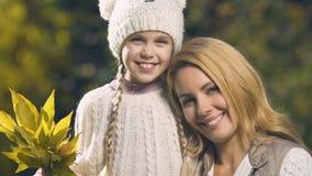 Μητέρα που αγκαλιάζει τη χαριτωμένη ανθοδέσμη εκμετάλλευσης κορών των φύλλων φθινοπώρου, φιλμ μικρού μήκους