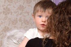 Μητέρα που αγκαλιάζει την λίγος άγγελος γιων Στοκ εικόνες με δικαίωμα ελεύθερης χρήσης