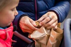 Μητέρα που ανοίγει ένα ψημένο κάστανο από μια πώληση σε μια αγορά Στοκ Εικόνα