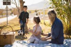 Μητέρα που αλληλεπιδρά με τα παιδιά στο πάρκο στοκ εικόνες