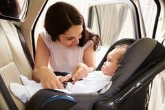 Μητέρα που βάζει το γιο μωρών στο κάθισμα ταξιδιού αυτοκινήτων Στοκ φωτογραφία με δικαίωμα ελεύθερης χρήσης