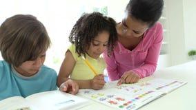 Μητέρα που βοηθά τα παιδιά με την εργασία απόθεμα βίντεο