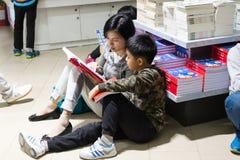 Μητέρα που βοηθά την ανάγνωση γιων στο βιβλιοπωλείο Στοκ Φωτογραφίες