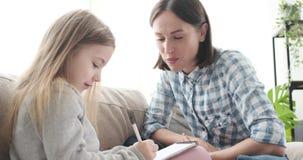 Μητέρα που βοηθά την κόρη που επισύρει την προσοχή στο σημειωματάριο απόθεμα βίντεο