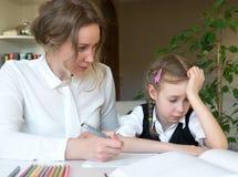 Μητέρα που βοηθά την κόρη με την εργασία Στοκ Φωτογραφία